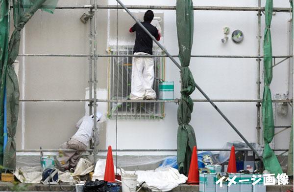 足場を組んで塗装する塗装職人